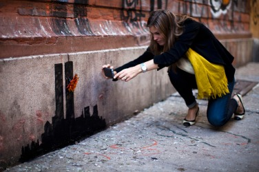 A woman takes a picture of an artwork by British graffiti artist Banksy at Lower Manhattan in New York City